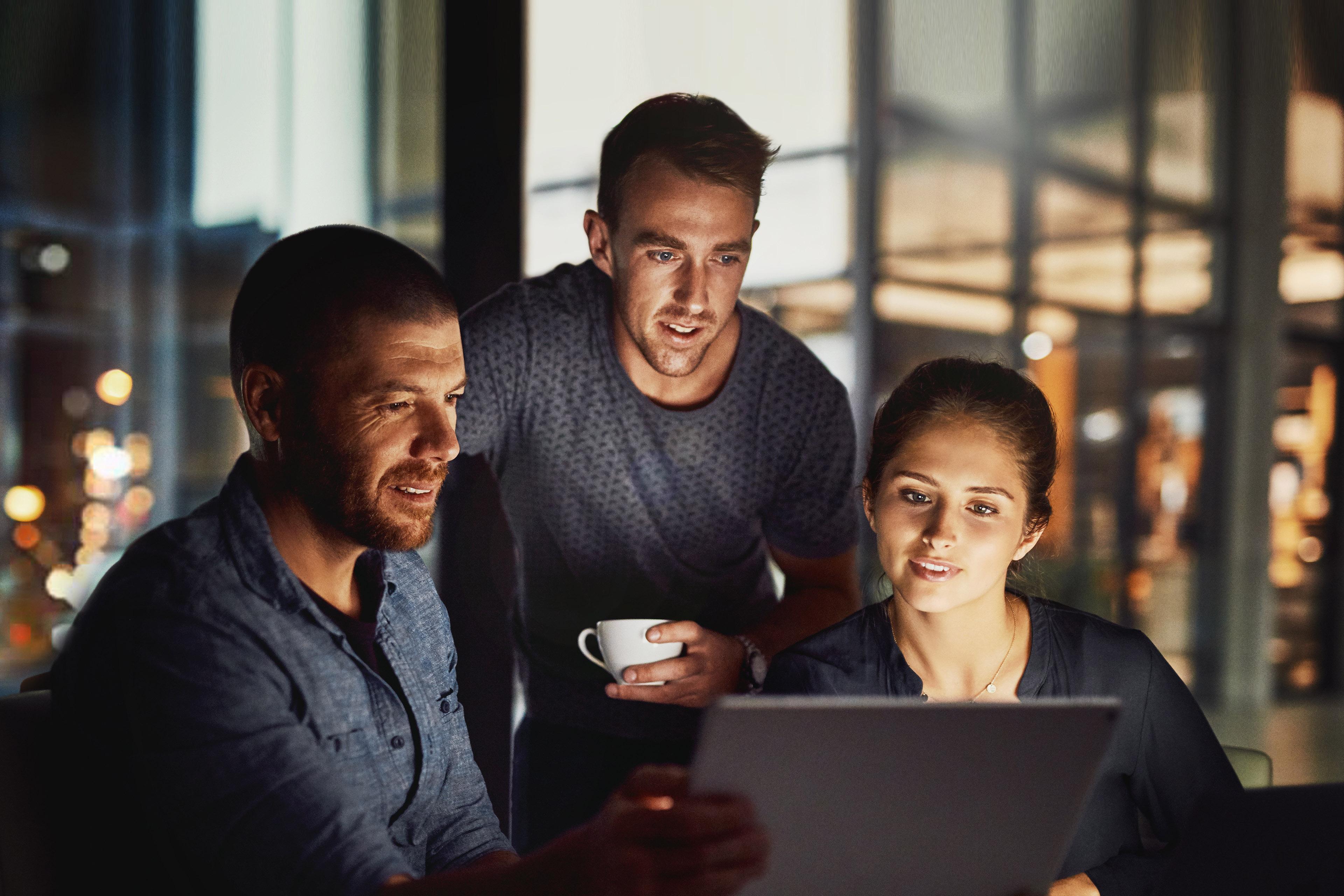 Eine Gruppe diskutiert das Projekt vor Laptop