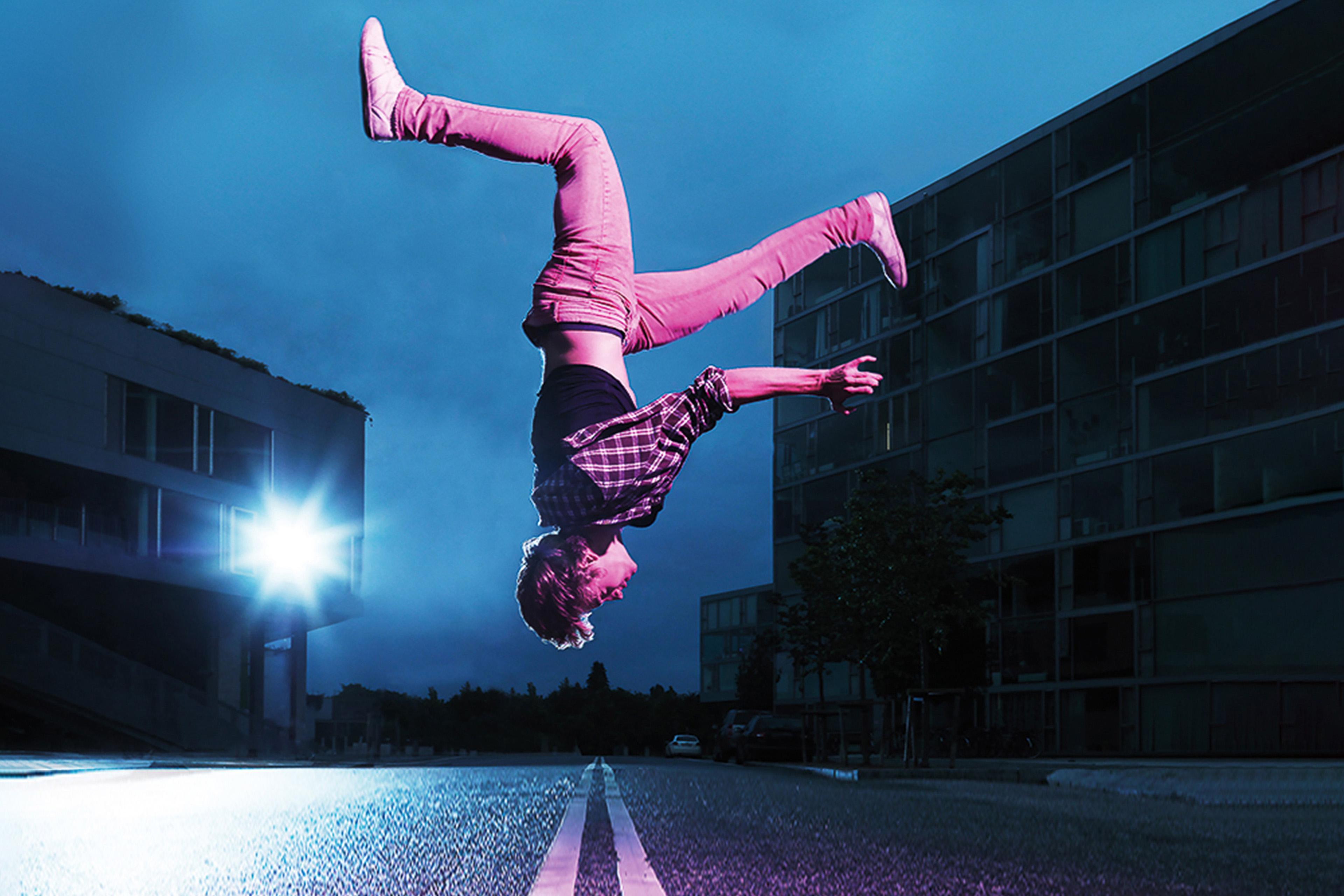 Mann macht einen Salto auf der Straße
