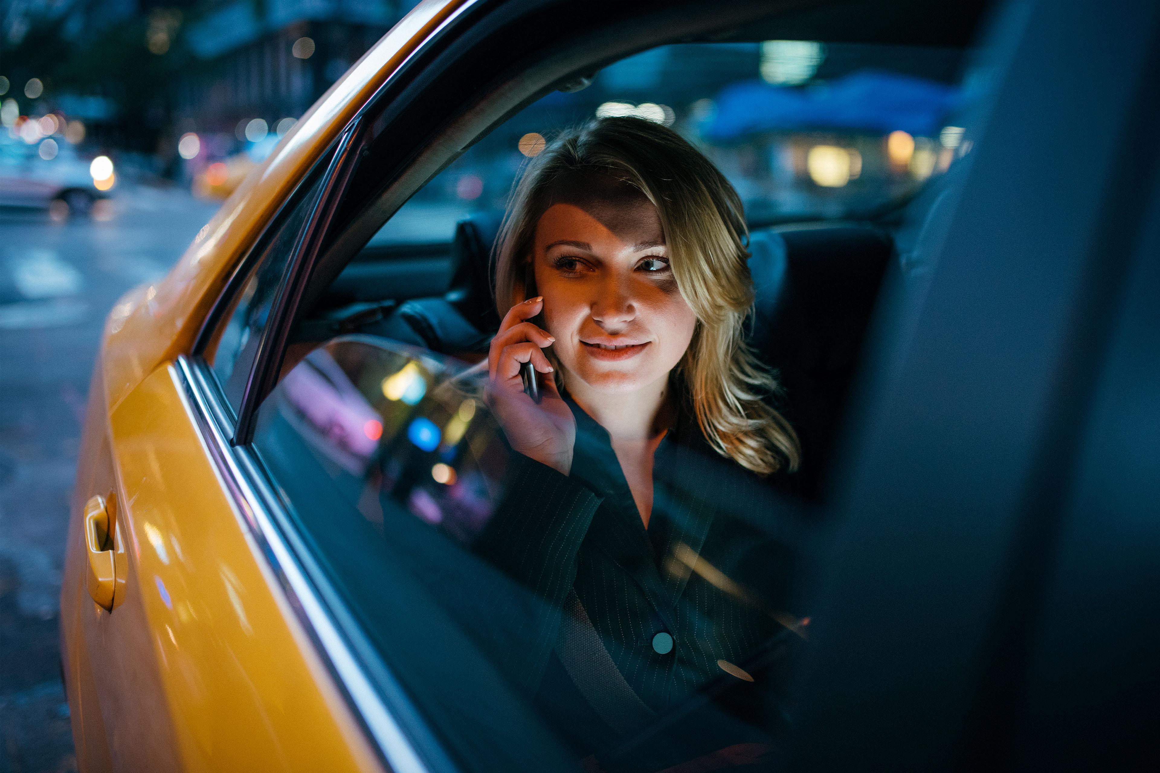 Frau telefoniert am Handy im Taxi