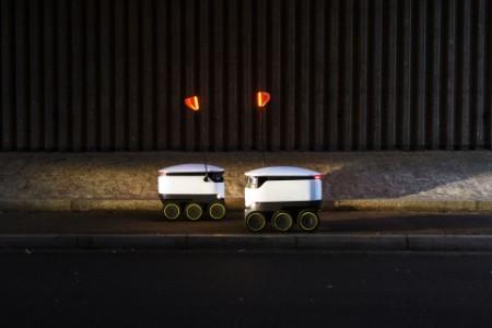 Zwei Lieferroboter fahren auf dem Bürgersteig